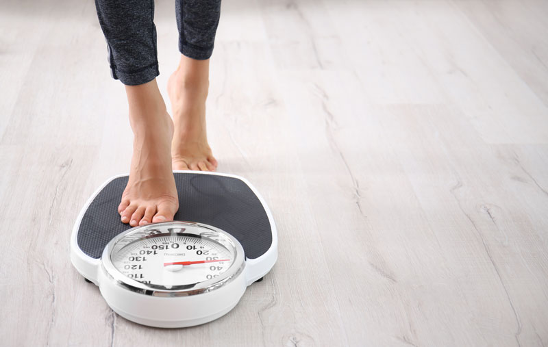 Woman stepping onto a scale