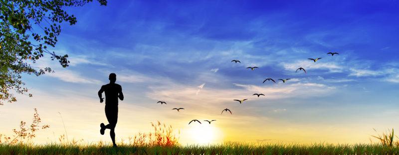 Man jogging at sunrise as a representation of physical health, mental health, and spiritual health